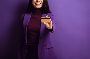 Cropped view of smiling woman showing credit card on purple background stock vector