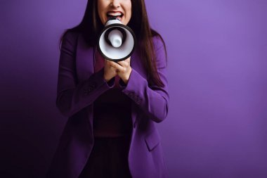Cropped view of excited woman screaming in megaphone on purple background stock vector