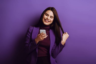 Happy young girl touching hair and smiling while chatting on smartphone on purple background stock vector