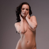 sexy and naked woman looking at camera isolated on grey