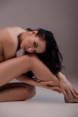szexi és meztelen nő ül szürke háttér