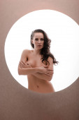 sexy and naked woman obscuring breast isolated on white in circle