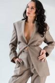 stylische und sexy Frau im Anzug schaut isoliert von grau weg