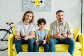 Kijev, Ukrajna - január 28, 2020: boldog homoszexuális pár és vegyes fajú gyerek videojáték