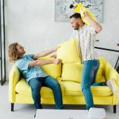 boční pohled na veselý homosexuální muži polštář boj v obývacím pokoji