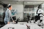 usmívající se asijská podnikatelka při pohledu na robota sedí za stolem v kanceláři