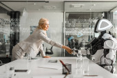 Photo smiling businesswoman shaking hands with robot sitting at desk in meeting room