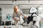 Photo attractive businesswoman holding digital tablet while operating robot