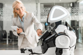 Photo smiling businesswoman operating robot while holding digital tablet