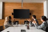 mladí multikulturní podnikatelé tleskají, když sedí v konferenčním sále a dívají se na obrazovku na zdi