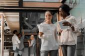Fotografie mladé africké americké a asijské podnikatelky s digitálním tabletem a dokumenty stojící v úřadu s multikulturními kolegy na pozadí