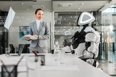 selective focus of smiling asian businesswoman holding digital tablet while looking at robot