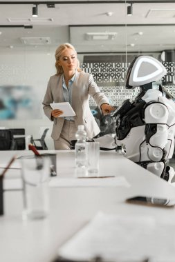 selective focus of attractive businesswoman operating robot while holding digital tablet