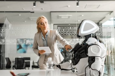 attractive businesswoman holding digital tablet while operating robot