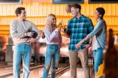 šťastný multikulturní přítel mluvení a cinkání lahví piva v luku klubu