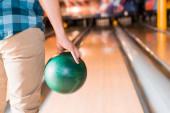 částečný pohled na mladého muže držícího bowlingovou kouli v blízkosti kuželkové uličky