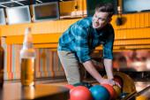 selektivní zaměření pohledný usmívající se muž s bowlingovou koulí v bowlingovém klubu