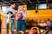 selektivní zaměření mladého muže a ženy mluvit při držení bowlingových míčků v bowlingovém klubu