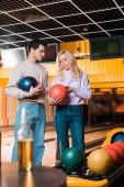 mladý muž a žena mluví při držení bowlingových koulí v bowlingovém klubu