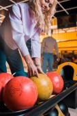 usmívající se blondýnka dívka výběru bowling koule v bowling klubu