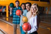 šťastný multikulturní přátelé drží bowlingové koule a při pohledu na kameru při stání v bowlingovém klubu