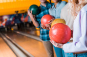 oříznutý pohled multikulturních přátel držících bowlingové koule při stání v bowlingovém klubu