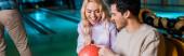 panoramatický záběr veselého páru při pohledu na bowling koule při sezení v bowlingovém klubu
