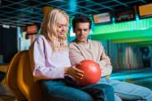usmívající se dívka ukazuje bowling koule na přemýšlivý přítel v bowling klubu