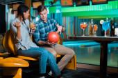 mladý muž ukazuje bowling míček na usmívající se africké americké dívky držící koktejl