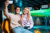glücklicher junger Mann zeigt Siegergeste, während er im Boxclub sitzt und ein Selfie mit seiner lächelnden Freundin macht