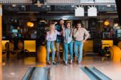 čtyři veselé multikulturní přátelé stojící v blízkosti kuželkárny v bowlingovém klubu