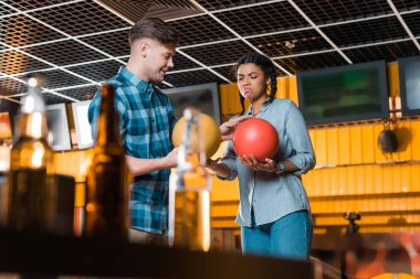 selective focus of smiling man talking to displeased african american girl while holding bowling balls