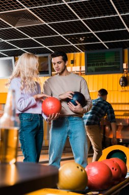 Handsome man talking to blonde girlfriend while holding bowling balls stock vector