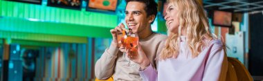 Panoramic shot of cheerful couple sitting in bowling club and drinking cocktails stock vector