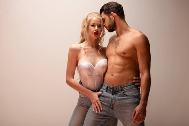 muscular man standing near sexy woman in jeans on grey