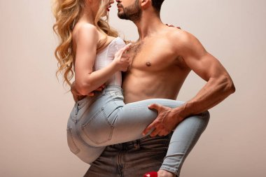 cropped view of muscular man touching leg of sexy woman in jeans isolated on grey