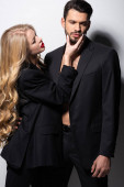 beautiful woman touching face of bearded man on white