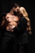 junge und schöne Frau berührt sexy Mann isoliert auf schwarz