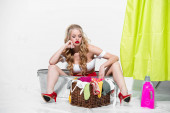 Photo displeased pin up woman in swimsuit looking at dirty laundry in basket on white