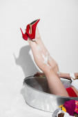 Photo cropped view of pin up woman in red high heels on white