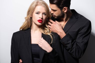 bearded man looking at attractive girlfriend with red lips on white