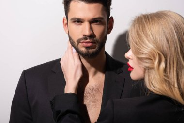attractive woman with red lips touching handsome boyfriend on white