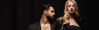 panoramic shot of attractive woman standing near bearded man isolated on black
