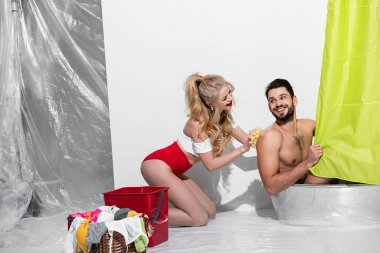 happy pin up woman washing handsome man with sponge on white