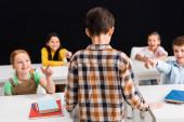 pohled zezadu na školáka stojícího poblíž školáků ukazujícího prsty izolovanými na černém, šikanujícím konceptu