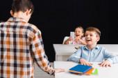 selektivní zaměření školačky fotografování spolužáka, zatímco školák se směje izolovaně na černošky, kyberšikana koncept