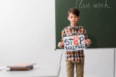 selective focus of schoolboy holding placard with stop bullying lettering in classroom