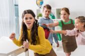 selective focus of cruel schoolkids touching backpack of bullied schoolgirl