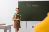 selective focus of sad schoolgirl standing near chalkboard with class work lettering