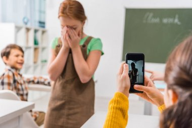 selective focus of schoolgirl taking photo of classmate, cyberbullying concept